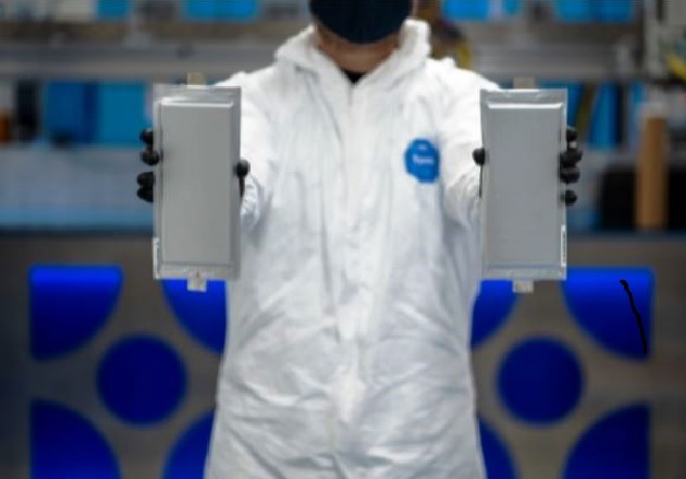 A Solid Power manufacturing engineer holds two 20-ampere hour (Ah) all-solid-state battery cells produced on its Colorado-based pilot production line. Image used courtesy of Solid Power