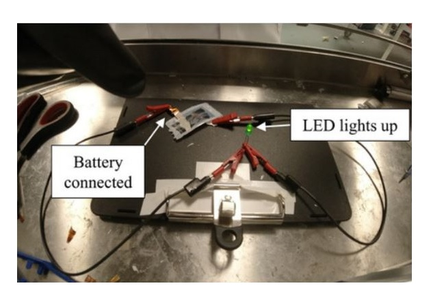 The structural battery cell connected to a circuit lights up a light emitting diode (LED) when exposed to mechanical loading. Image used courtesy of Chalmers University of Technology