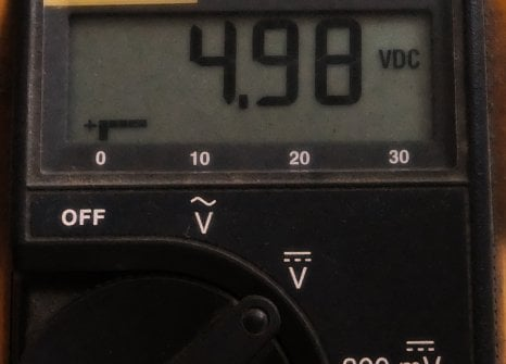 A voltage measurement shown on the digital display of a multimeter.