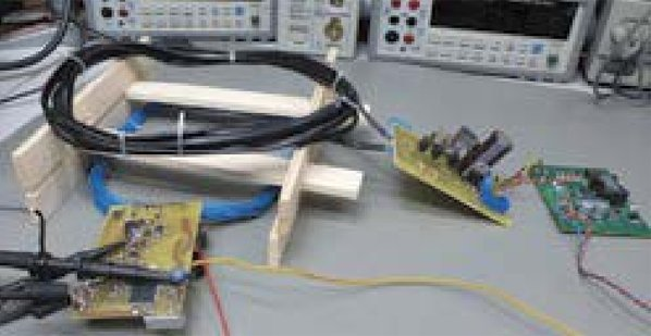 """One example of """"uniWP"""": Transmitter with blue loop antenna, receiver with black loop antenna, synchronous rectification board and buck-boost-converter for a controlled output, here 24 Volt."""